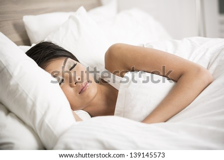 Portrait of a beautiful young Chinese female sleeping in bed at home - stock photo