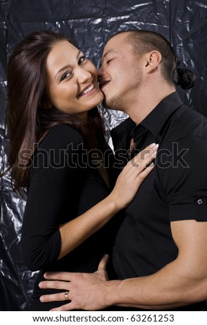 Portrait of a beautiful young couple about to kiss against black background - stock photo