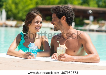 Portrait of a beautiful young couple enjoying a cocktail on the poolside - stock photo