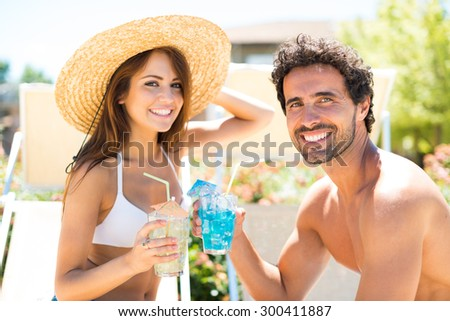 Portrait of a beautiful young couple enjoying a cocktail while talking - stock photo