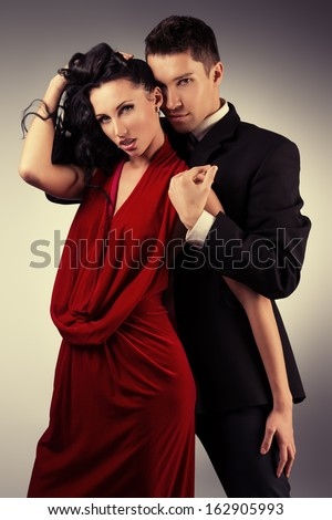 Portrait of a beautiful young couple in love posing at studio. - stock photo