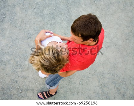 Portrait of a beautiful young couples are happily embracing at walk. Top view - stock photo