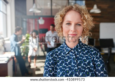 Portrait of a beautiful young female designer in office with some colleagues discussing in the background. - stock photo