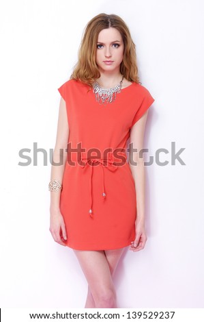 portrait of a beautiful young female in red dress standing posing - stock photo