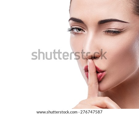Portrait of a beautiful young girl , Europeans , shot close-up , clear skin , a gesture index finger pressed to his lips , secret , silence , secrecy .space for text - stock photo