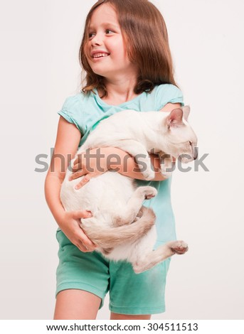 Portrait of a beautiful young girl holding a siamese cat. - stock photo