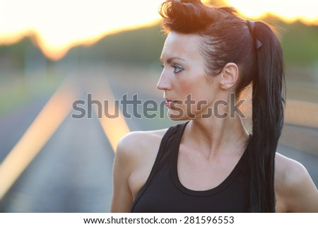 Portrait of a beautiful young girl in a black shirt on a railway track at sunset - stock photo