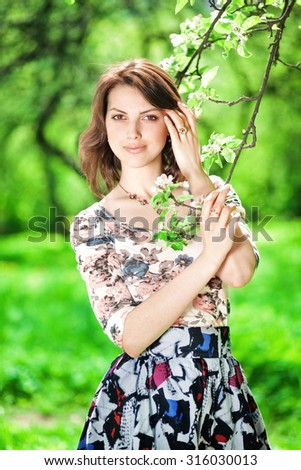 Portrait of a beautiful young girl in a positive mood calm against the bright eternal bright green in the park - stock photo