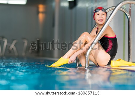 Portrait of a beautiful young girl in a red cap at the swimming pool with flippers - stock photo