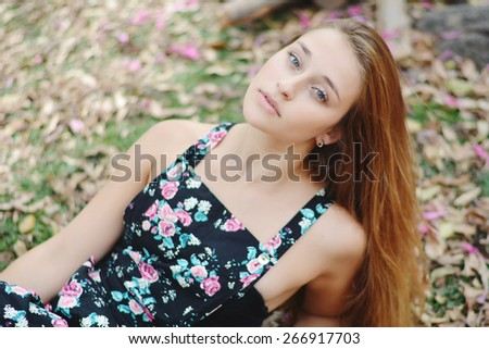 Portrait of a beautiful young girl in park in spring - stock photo