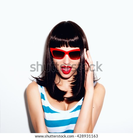 Portrait of a beautiful young girl in sunglasses and striped shirt in the studio on a white background - stock photo