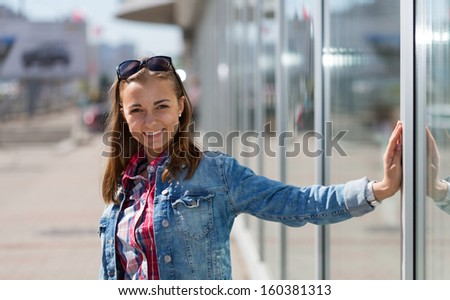 Portrait of a beautiful young girl on the street, squinting in the bright sun. - stock photo
