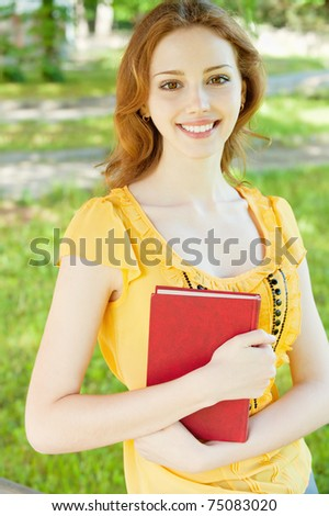 Portrait of a beautiful young girl-student with a book on the background of green nature - stock photo