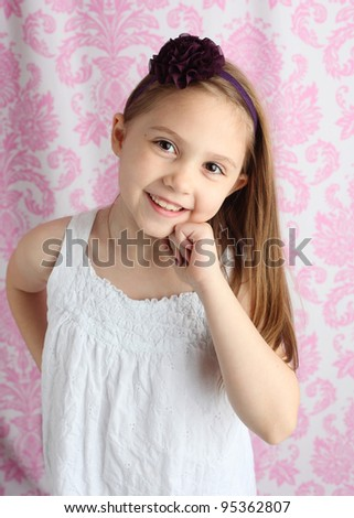 Portrait of a beautiful young girl wearing a purple flower hair bow with pink damask background in studio - stock photo