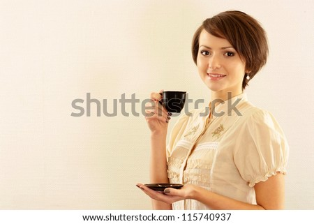 Portrait of a beautiful young girl with a cup on a beige - stock photo