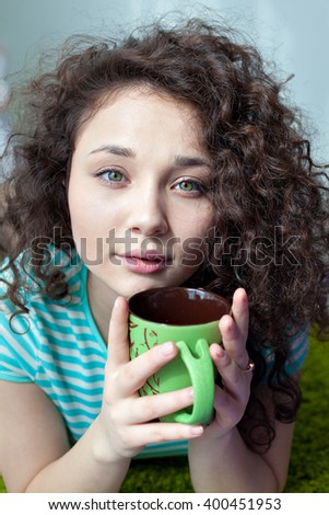 Portrait of a beautiful young girl with brown curly hair. Drink your morning coffee. Girl with a cup of tea in his hands looking at the camera. Big green eyes and green cup in his hands. - stock photo