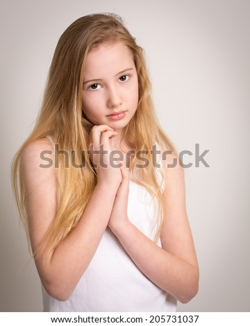 Portrait of a beautiful young girl with long blond hair and bare shoulders isolated against a grey background - stock photo