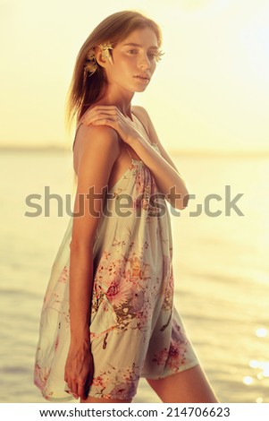 Portrait of a beautiful young girl with red hair, walking along the beach - stock photo