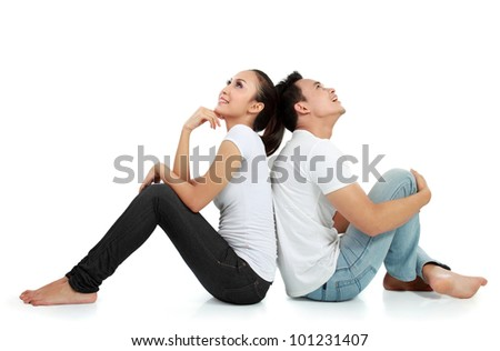 Portrait of a beautiful young happy couple sitting on the floor thinking something - stock photo