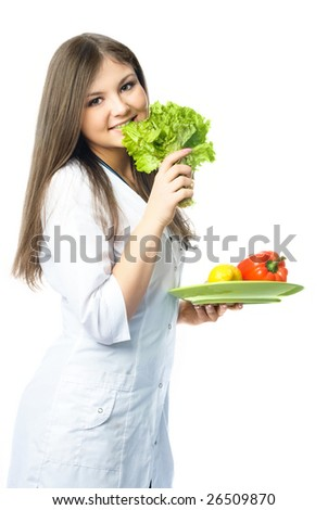 portrait of a beautiful young happy doctor eating fresh vegetables - stock photo