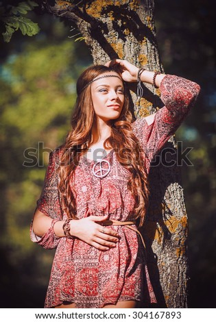 Portrait of a beautiful young hippie girl standing near tree - stock photo