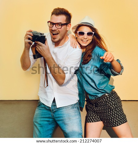 Portrait of a beautiful young hipster couple. Positive guy in a shirt and jeans. Girl in hat and sunglasses smiling against a yellow background outdoor - stock photo