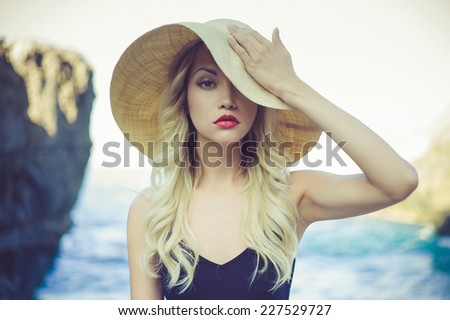 Portrait of a beautiful young lady in a straw hat - stock photo