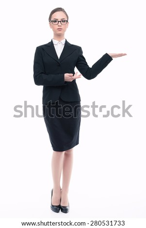 Portrait of a beautiful young lady wearing glasses formal jacket white shirt and a black skirt, standing full length and holding copy space isolated on white background - stock photo