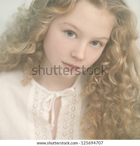 portrait of a beautiful young lady with curly blonde hair and a gentle manner - stock photo