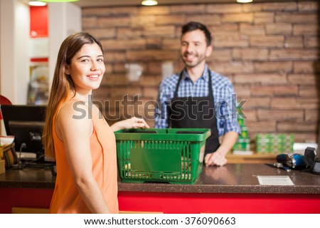 Portrait of a beautiful young Latin brunette paying for her groceries at the checkout counter in a store - stock photo