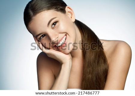 Portrait of a beautiful young Latina girl toothy smiling / photograph of a cute brunette smiling girl on studio background  - stock photo