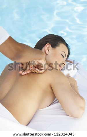 Portrait of a beautiful young Latina Hispanic woman eyes closed laying down, relaxing and having a massage by a swimming pool at a health spa - stock photo
