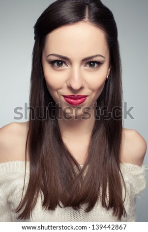 Portrait of a beautiful young long-haired brunette smiling and posing over light-gray background. Healthy skin. Studio shot - stock photo