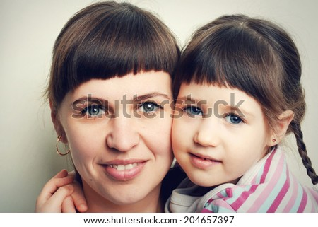 Portrait of a beautiful young mother and cute little daughter - stock photo