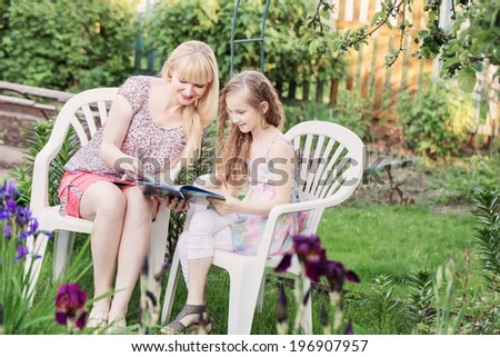 portrait of a beautiful young mother and her daughter reading book in garden - stock photo
