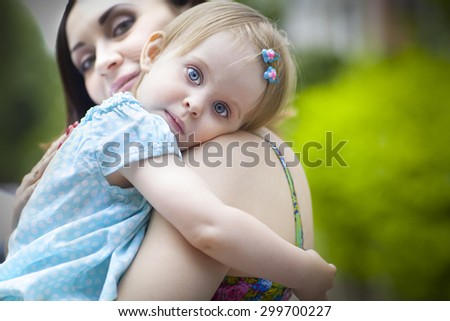 Portrait of a beautiful young mother with daughter in summer park - stock photo