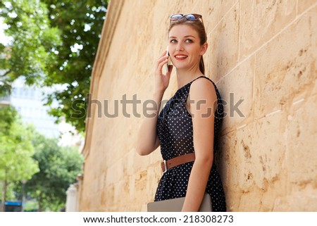 Portrait of a beautiful young professional businesswoman using a smart phone technology to make a phone call while leaning on a textured stone wall in a financial city. Lifestyle outdoors. - stock photo