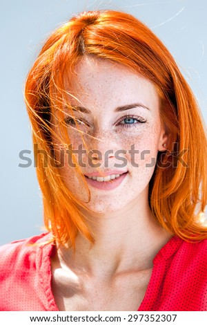 Portrait of a beautiful young redhead woman with blue eyes and freckles - stock photo