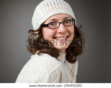 Portrait of a beautiful young smiling brunette wearing chochet hat and spectacles on studio grey background - stock photo