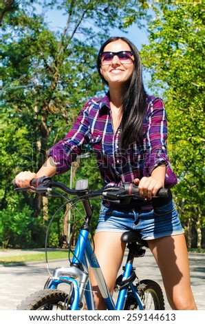 Portrait of a beautiful young smiling woman on a bicycle - stock photo