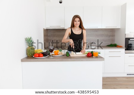 Portrait of a beautiful young smiling woman. Young girl cooking in the new kitchen. Preparing vegetable salad. - stock photo