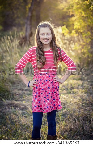 Portrait of a beautiful young teenage girl outdoors standing and smiling during an autumn afternoon - stock photo