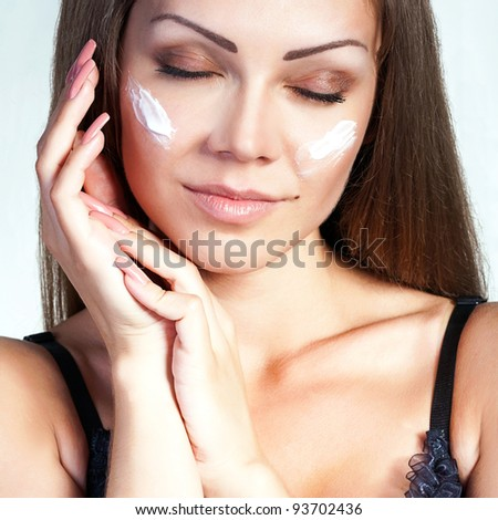 Portrait of a beautiful young woman applying face cream on her cheek - stock photo