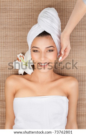 portrait of a beautiful, young woman, at a spa, lying on her back on a bamboo mat, with a towel in her head, smiling, with a lily near her head and the hand of the spa therapist applying a face cream - stock photo