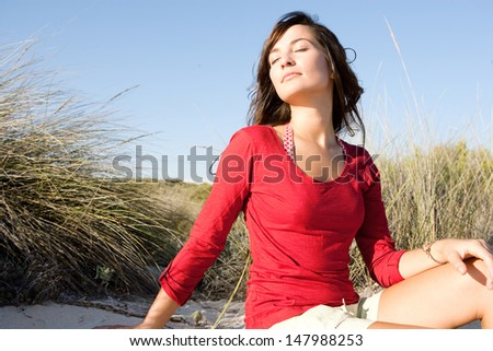 Portrait of a beautiful young woman breathing fresh air while sitting on a beach sand dunes with grass, leaning her head back and enjoying the breeze on vacation. - stock photo