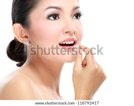 Portrait of a beautiful young woman consume pill isolated on white background - stock photo