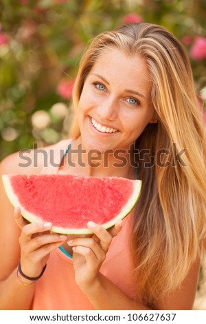 Portrait of a beautiful young woman eating watermelon - stock photo