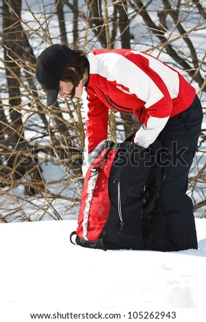 Portrait of a beautiful young woman going on trip with sporty clothes, cap, leaning down, looking for something in her rucksack - stock photo