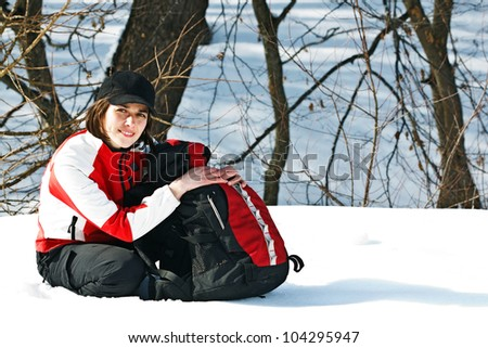 Portrait of a beautiful young woman going on trip with sporty clothes, cap, rucksack, sitting next to her rucksack, smiling into camera - stock photo