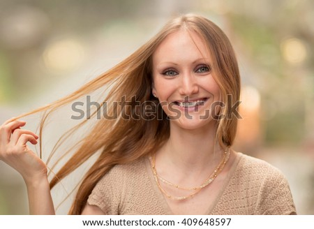 Portrait of a beautiful young woman grabbing her long blonde hair with her hand; haircare concept - stock photo
